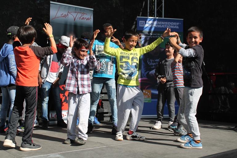 """Die Friedensdorf-Kinder zeigen bei ihrem Flashmob ihre Tanzkünste und stecken bei dem Song """"Happy"""" gleich mit ihrer Lebensfreude das Publikum an."""